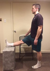 picture demonstrating how to stretch the hamstring muscles with help of a bench